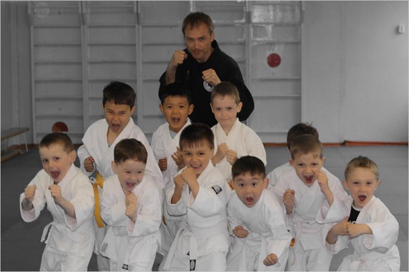 сенсей проводит уроки детям в секции каратэ